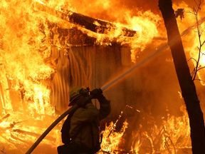 A firefighter battles a wild fire blaze in Magalia, California