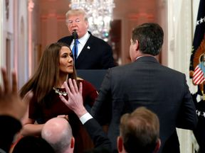 CNN's Jim Acosta refuses to relinquish the microphone to a White House staffer