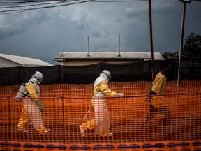Two medical staff walk with a man in the Ebola treatment area of Bunia