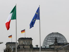 The national flags of Italy and Germany and the EU flag are pictured atop the Reichstag building