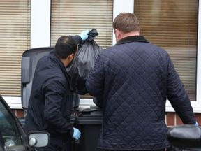 Officers examine the contents of bins outside a house being searched in connection with the bonfire