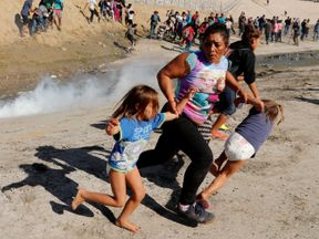 A migrant family from Honduras, runs from tear gas released by U.S. border patrol near the fence between Mexico and the United States in Tijuana