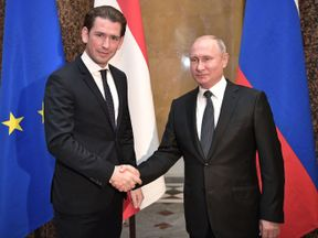 Russian President Vladimir Putin (R) shakes hands with Austrian Chancellor Sebastian Kurz during a meeting at the State Hermitage Museum in Saint Petersburg on October 3, 2018
