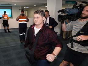 Renae Lawrence charges through a large media pack at Newcastle Airport on November 22, 2018 in Newcastle, Australia