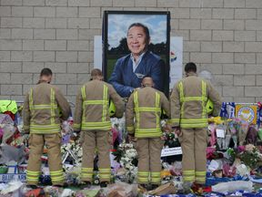 Firefighters pay their respects in front of a portrait of Vichai Srivaddhanaprabha