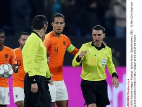 Virgil van Dijk of Holland gives a hug and consoles referee Ovidiu Hategan at the end of the match
