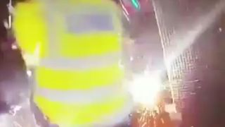 Police officers in Enfield move quickly as a firework is thrown at them in the street