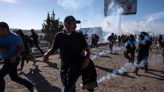 Migrants run along the Tijuana River after the US border patrol throw tear gas