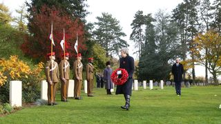 Theresa May lays a wreath at the graves of John Parr, the first British soldier to be killed in 1914, and George Ellison, the last to be killed