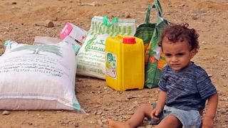 A displaced child from Hodeida sits next to food aid