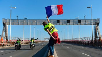 man waves a French flag on the rocade (ring road) during a demonstration of Yellow Vests (Gilets jaunes) against the rising of the fuel and oil prices on November 17, 2018 in Bordeaux, southwestern France