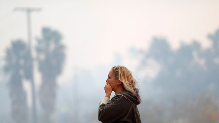 A woman reacts as the Woolsey Fire burns in Malibu, California
