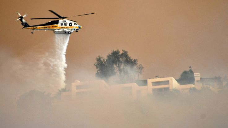 A Los Angeles County Fire Department firehawk makes a water drop through the thick smoke on homes in the hills of Malibu