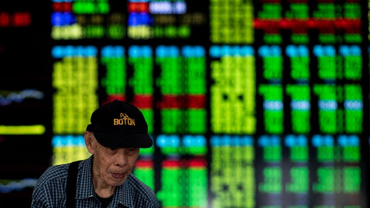 An investor walks past stock prices monitors at a securities company in Shanghai on September 25, 2018
