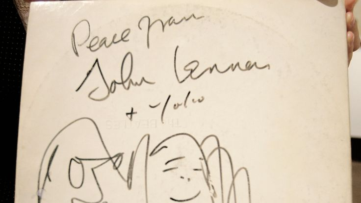 A Beatles White Album, signed and drawn on by John Lennon and Yoko Ono in 1969, is held on display at Christie's Auction House, November 21, 2005 in New York City