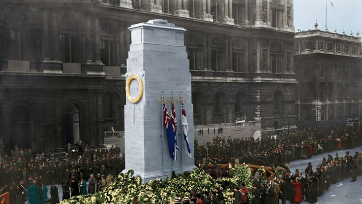 Members of the public filing past the wreath laden base of the Cenotaph on Armistice Day
