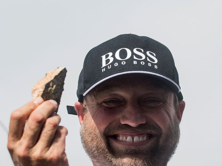 Alex Thomson holds up a piece of rock he picked up after his collision