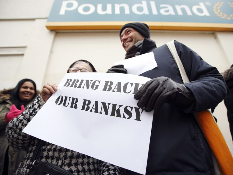 Bring Back Our Banksy: Residents protest next to a section of a wall where street artist Banksy's 'Slave Labour' graffiti artwork was removed in north London in February 2013
