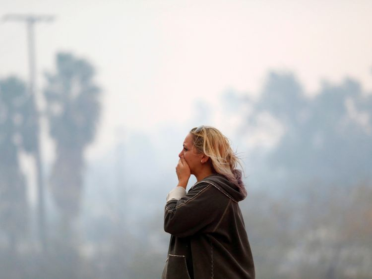 A woman reacts as the Woolsey Fire burns in Malibu, California, U.S. November 9, 2018