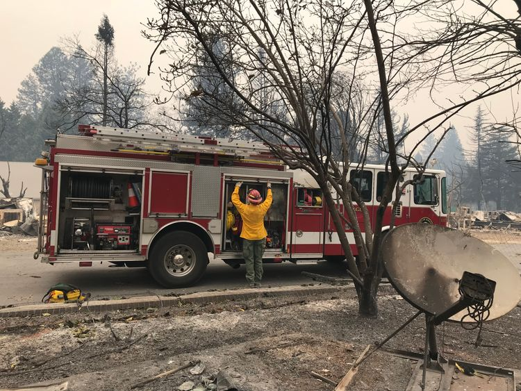 A firefighter works in one of the areas burned out in Paradise