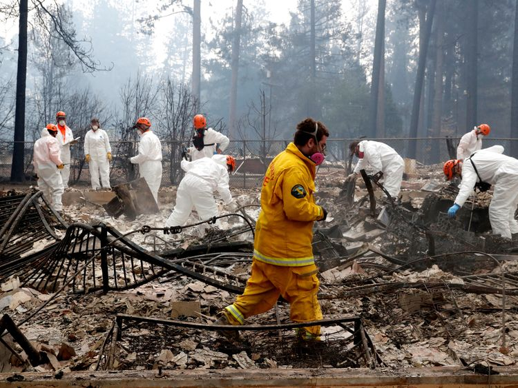 Firefighters and members of a volunteer search and rescue crew approach a house destroyed by the Camp Fire in Paradise, California, U.S., November 13, 2018. REUTERS/Terray Sylvester