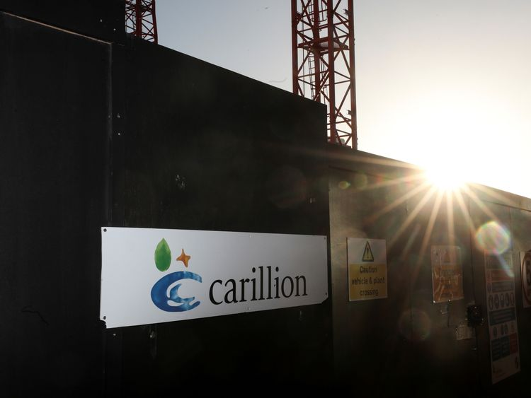 A logo is seen in front of cranes standing on a Carillion construction site in central London