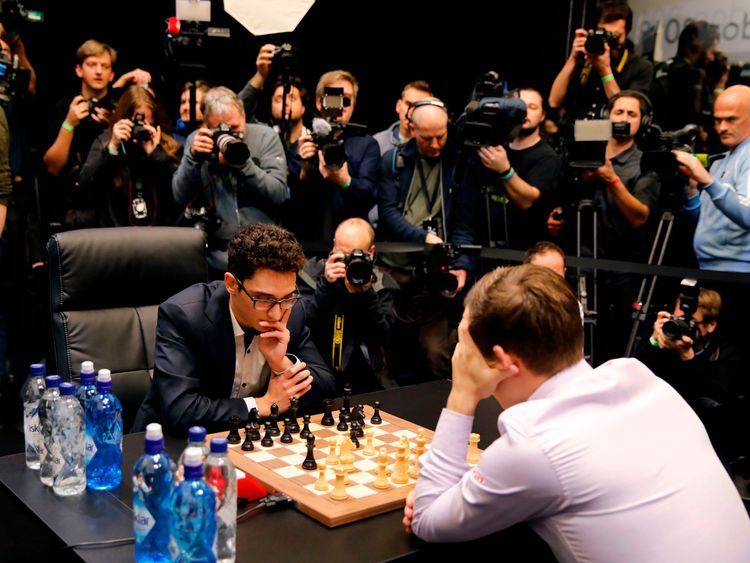 Magnus Carlsen (R) and Fabiano Caruana (C) play the first tie-break match