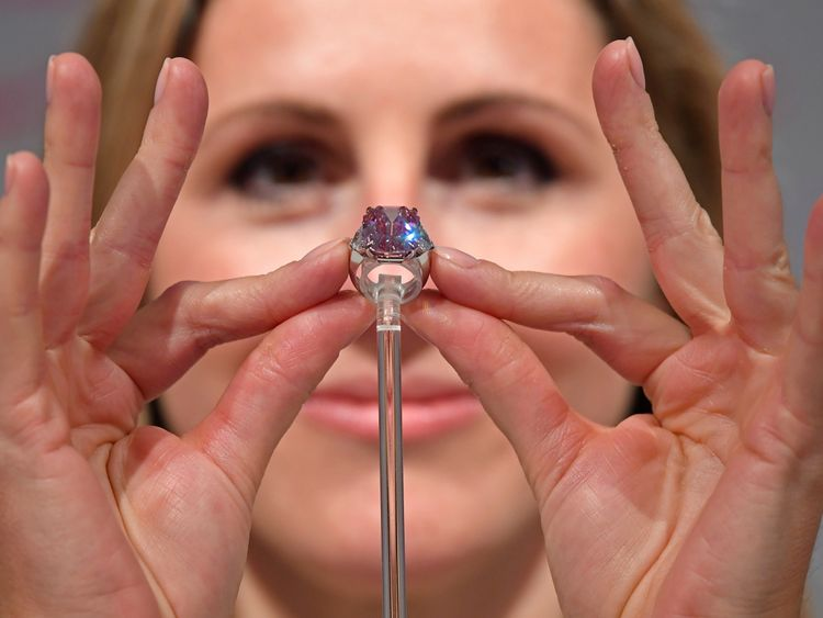 Jewellery Specialist at Christie's, Rachel Evans-Omeyer, poses with an 18.96 carat Fancy Vivid Pink Diamond prior to it being auctioned in November in Geneva, at Christie's in London, Britain, September 25, 2018. REUTERS/Toby Melville