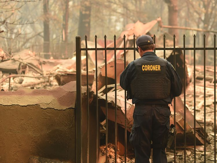An Alameda County Sheriff Coroner officer looks for human remains at a burned residence in Paradise, California on November 12, 2018. - Thousands of firefighters spent a fifth day digging battle lines to contain California's worst ever wildfire as the wind-whipped flames cleaved a merciless path through the state's northern hills, leaving death and devastation in their wake. The Camp Fire -- in the foothills of the Sierra Nevada mountains north of Sacramento -- has killed 29 people, matching the