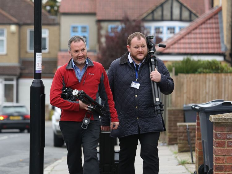 Police investigators arrive outside a house being searched in connection with the video