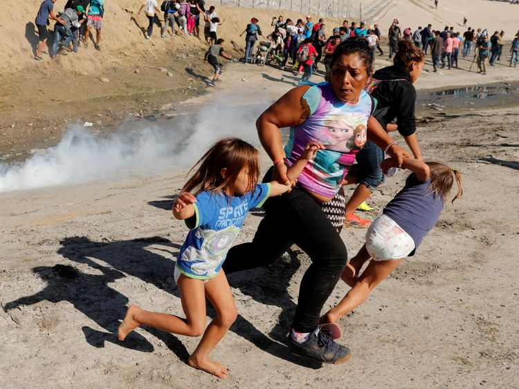 A migrant family from Honduras runs from tear gas released by U.S. border patrol near the fence between Mexico and the United States in Tijuana