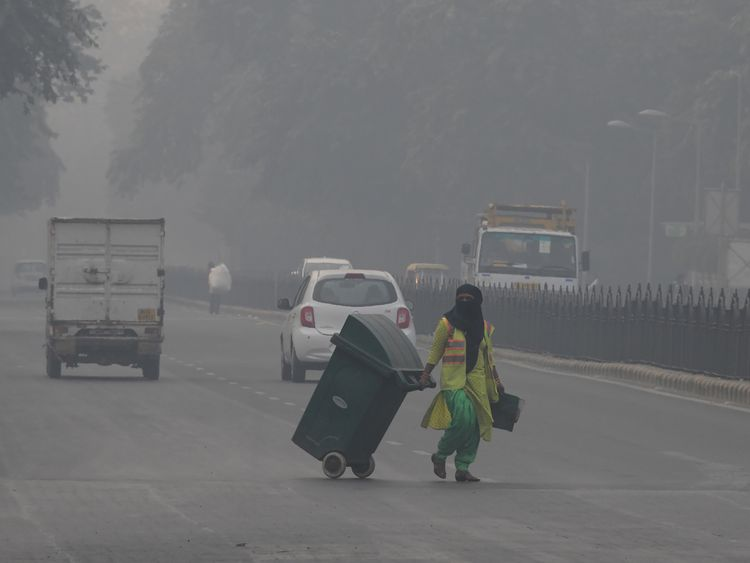 A sweeper cleans a road amid heavy smog