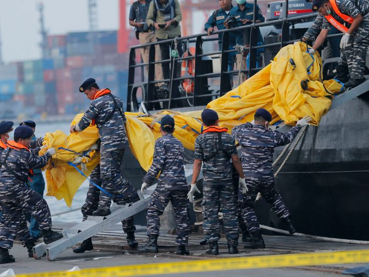Navy personnel remove recovered parts of the Lion Air jet
