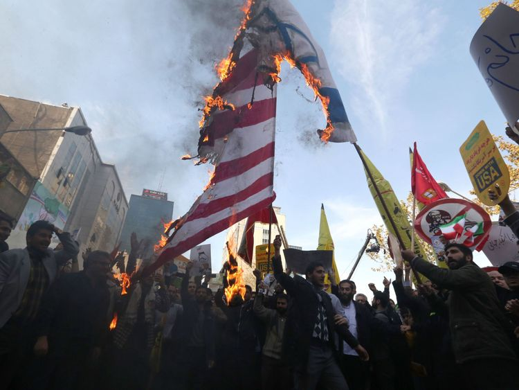 Protesters burn US and Israeli makeshift flags during a demonstration