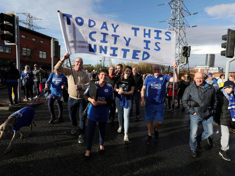 Fans carry a banner saying 'today this city is united' as thousands march to the stadium