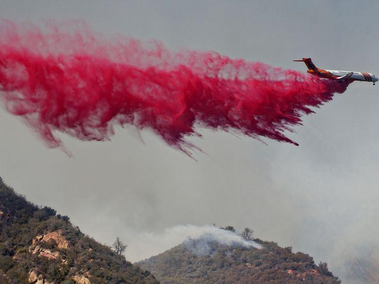 An air tanker drops fire retardant on flames on November 10, 2018 in Malibu, California