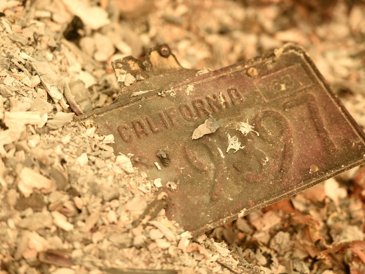 A car number plate partly buried in the remains of the town of Paradise