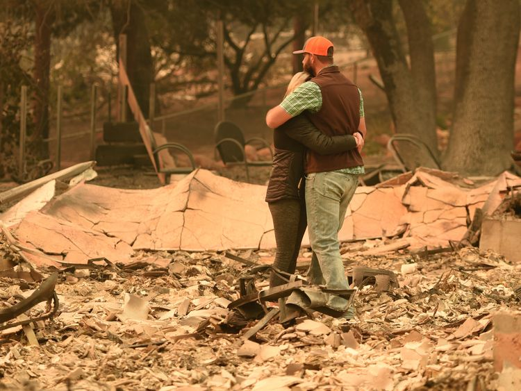 Chris and Nancy Brown embrace while looking over the remains of their burned house in Paradise