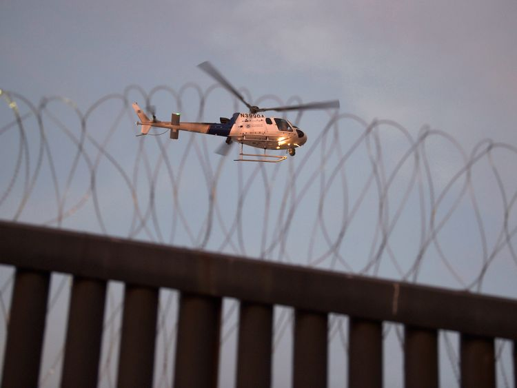 A US helicopter patrols the border with Mexico at Tijuana