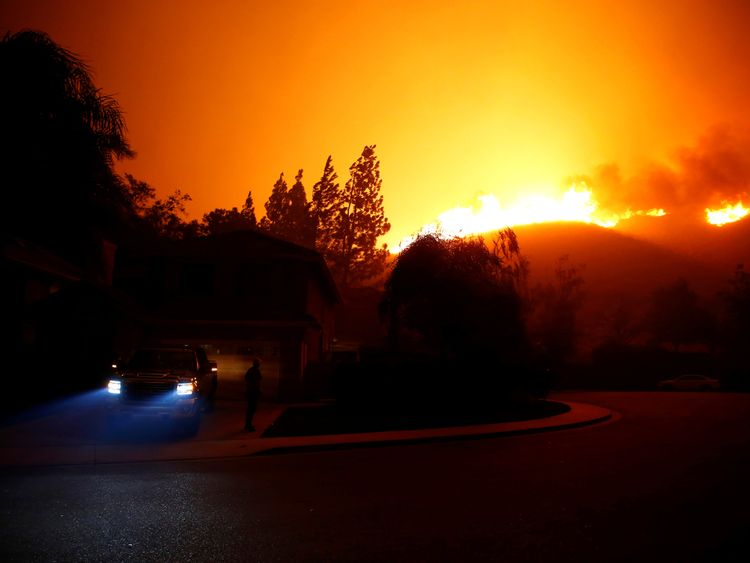 A resident looks at approaching flames as firefighters battle flames overnight during a wildfire that...