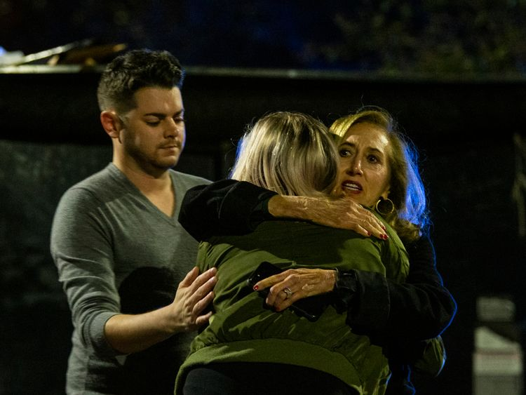 Matthew Rodin, left and Susan Turner comfort Melissa Hutchinson who helped some of the victims of the shooting