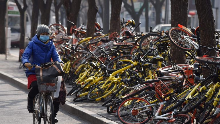A woman rides past shared bicycles piled beside a road in Beijing on February 21, 2018