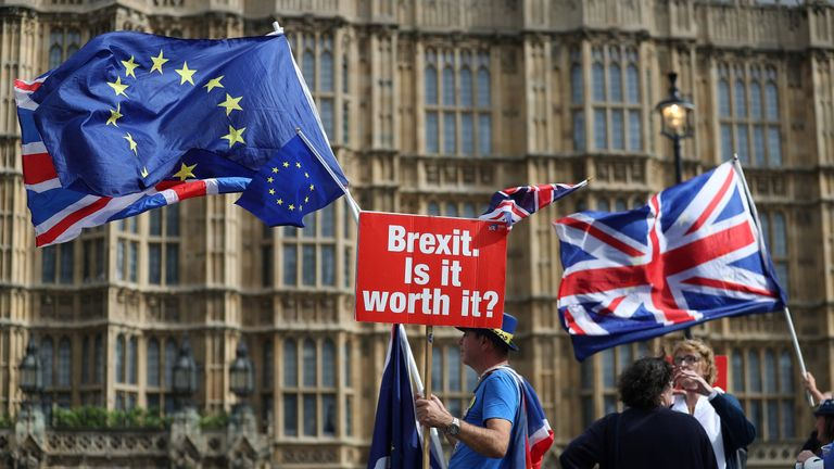 A demonstrator holds a sign that reads 'Brexit. Is it worth it?' whilst draped in European Union (EU) and Union flags, as he protests outside the Houses of Parliament in central London on September 10, 2018