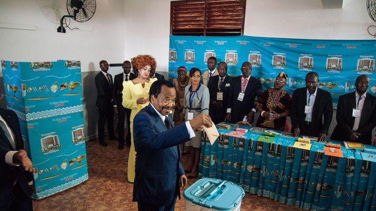 President Paul Biya casting his ballot as his wife Chantal looks on on 7 October