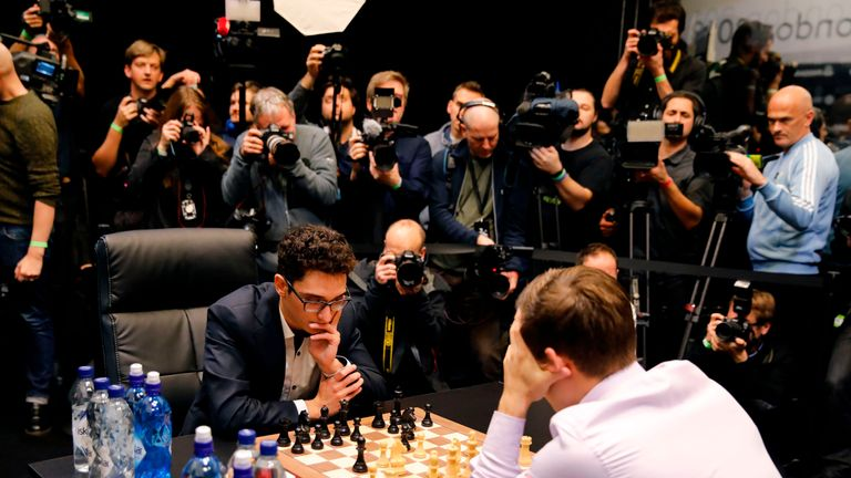 Magnus Carlsen (R) and Fabiano Caruana (C) playing the first tie-break match