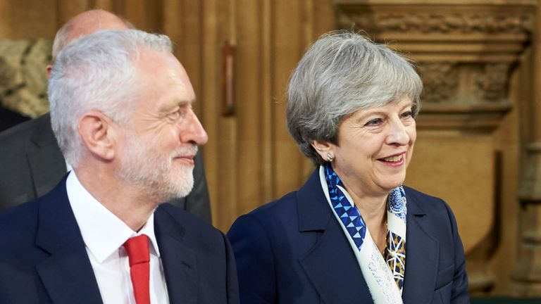 LONDON, UNITED KINGDOM - JUNE 21: Britain's Prime Minister Theresa May (R) and Britain's main opposition Labour Party leader Jeremy Corbyn (L) walk back across the Central Lobby of the Palace of Westminster from the House of Lords to the House of Commons after listening to the Queen's Speech during the State Opening of Parliament on June 21, 2017 in London, United Kingdom. This year saw a scaled-back State opening of Parliament Ceremony with the Queen arriving by car rather than carriage and not