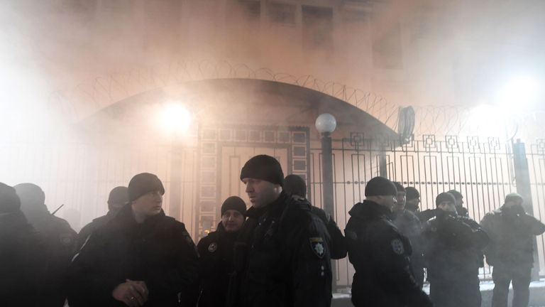 Police officers stand in front of the Russian Embassy in Kiev late on November 25, 2018, while smoke from a flare thrown by protesters is seen during a rally following an incident in the Black Sea off Moscow-annexed Crimea