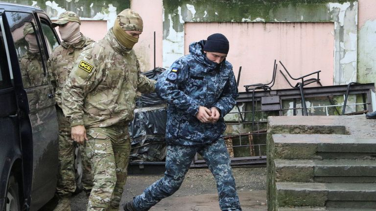 A member of Russia's FSB security service escorts a detained Ukrainian navy sailor before a court hearing in Simferopol, Crimea