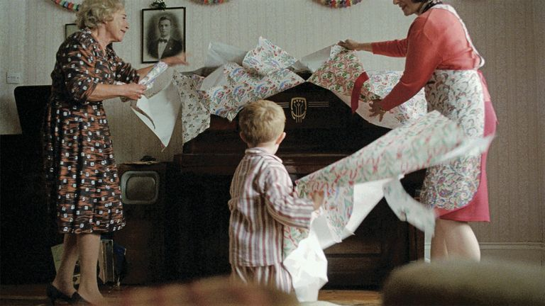 Elton unwraps his present with his mother and grandmother