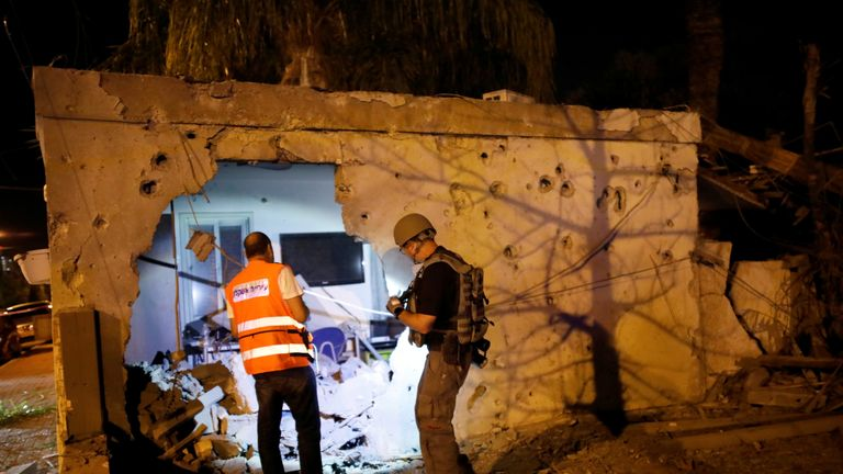 Security checks a damaged house in the Israeli city of Ashkelon after a Gaza rocket attack